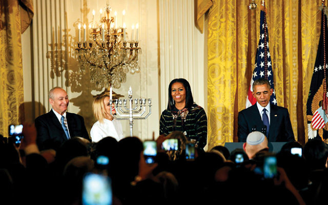 President Barack Obama, with wife Michelle, speaking at a Chanukah reception with the son and granddaughter of the late Israeli President Shimon Peres — Chemi Peres, left, and Mika Almog — at the White House. Aude Guerrucci-pool/Getty Images