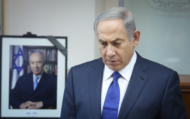 Israeli Prime Minister Benjamin Netanyahu in a moment of silence, as a photograph of former President Shimon Peres is displayed behind him, in Jerusalem, Israel, Sept 28, 2016. (Marc Israel Sellem/POOL/Flash90)