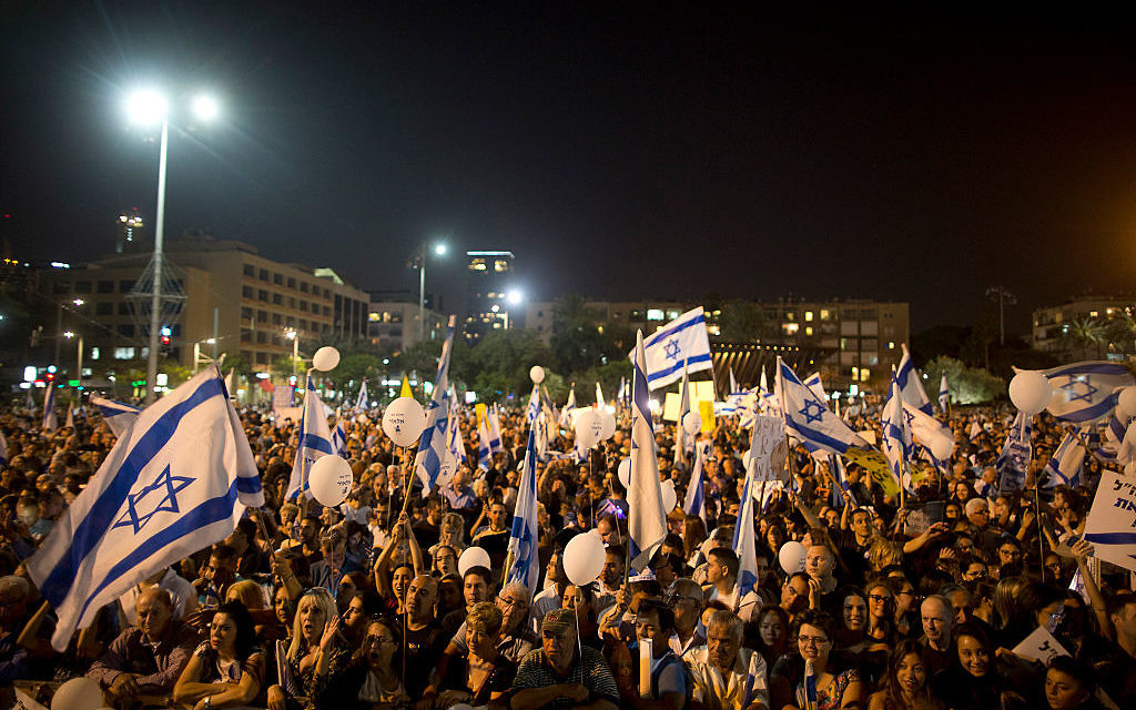 Israelis hold up flags during a rally in support of Israeli soldier Elor Azaria on April 19, 2016 in Tel Aviv, Israel. Getty Images