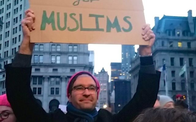 A man holds a sign protesting the ban on travel from seven Muslim countries at a rally in Battery Park NYC. Hella Winston/JW