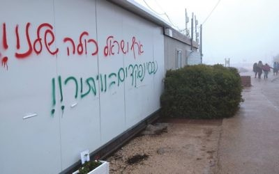 """""""All of the Land of Israel is Ours"""": Graffiti on a public meeting room at the Amona Outpost called the compromise this week to get the settlers there to leave voluntarily a """"concession."""" Joshua Mitnick/JW"""