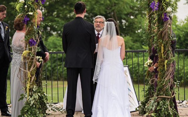 Conservative Rabbi Seymour Rosenbloom officiating at the wedding of his stepdaughter and her fiancé in 2014. He was expelled from the movement for his act.  Courtesy of Stefanie Fox via JTA