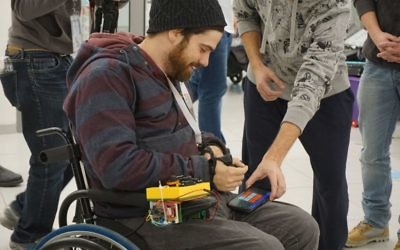 Chair Call: Drew McPherson, TOM:Berkeley Organizer at TOM:Israel in January designing a device to help call a power wheelchair to ones' bedside. Courtesy of Tikkun Olam Makers