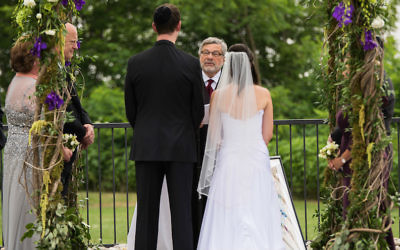 Rabbi Seymour Rosenbloom officiating at the wedding of his stepdaughter and her fiance in 2014. Courtesy of Stefanie Fox via JTA