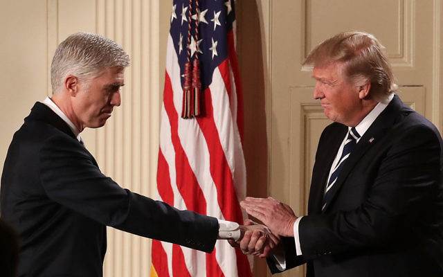 U.S. President Donald Trump (R) shakes hands with Judge Neil Gorsuch after nominating him to the Supreme Court during a ceremony in the East Room of the White House January 31, 2017 in Washington, DC. Getty Images