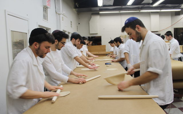 Workers roll matzah dough into thin, round discs at the Satmar Bakery in Brooklyn. (Uriel Heilman)
