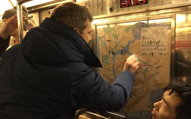 Commuters removing swastikas from a New York City subway, Feb. 4, 2017. JTA