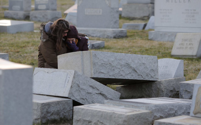 Melanie Steinhardt comforts Becca Richman at the Jewish Mount Carmel Cemetery, February 26, 2017, in Philadelphia, PA. Police say more than 100 tombstones were vandalized a week after a Jewish cemetery in St. Louis was desecrated. / AFP / DOMINICK REUTER        (Photo credit should read DOMINICK REUTER/AFP/Getty Images)