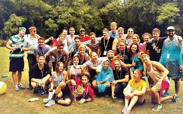 This summer, young adults can relive such Jewish summer camp favorites as Israeli dancing, gaga and, of course, color war. Above, a color war team poses during a Moishe House event. SCOTT SPORLEDER