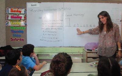 Casey Spellman teaches a 5th grade class a song to help them remember how to spell the word chicken at the Rimalt school in Netanya.   COURTESY OF CASEY SPELLMAN