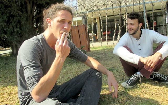 Amit Meyer, a physics student at Hebrew University, smokes a hand-rolled tobacco cigarette. Michele Chabin/JW
