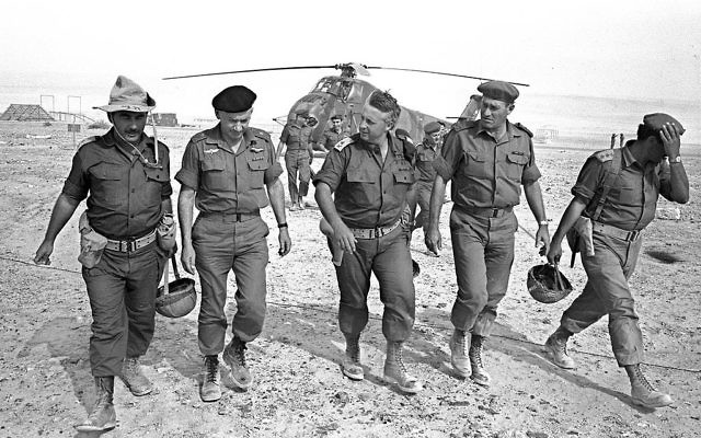Israeli Army Gen. Ariel Sharon (C), flanked by Gens. Haim Bar-Lev (L) and Yishayahu Gavish (R) and unidentified aides, arrives by helicopter at an army base June 1, 1967  in Israel's Negev Desert. David Rubinger/GPO/Getty Images