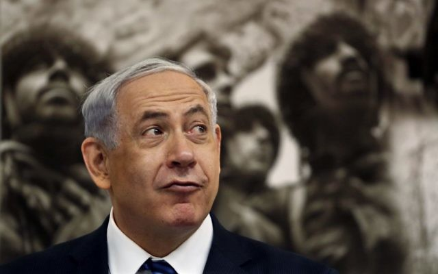 Backdropped by Israeli photographer David Rubinger's iconic picture from 1967 Six Day War of Israeli paratroopers at the Western Wall, Israeli Prime Minister Benjamin Netanyahu opens a special Jerusalem Day Cabinet Meeting at Ammunition Hill on May 28, 2014.  Getty Images