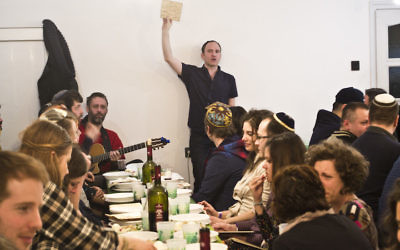 Adam Schonberger, standing, with other participants at the 2016 seder dinner at the Aurora Jewish community center in Budapest, April 22, 2016. JTA