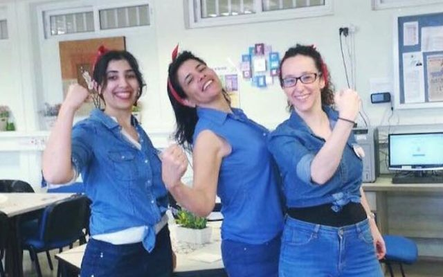 Shir Yorkevitz, right, and two other teachers dressed as Rosie the Riveter flexing at a middle school in Herzliya, Israel, March 8, 2017. (Courtesy of Shir Yorkevitz)