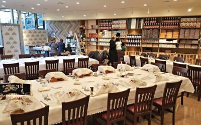 The Masbia dining room in Borough Park, with tables set for Shabbos. The addition of Shabbos meals at that location inspired the group's co-founder, Alexander Rapaport, to serve Passover meals. Courtesy of Masbia