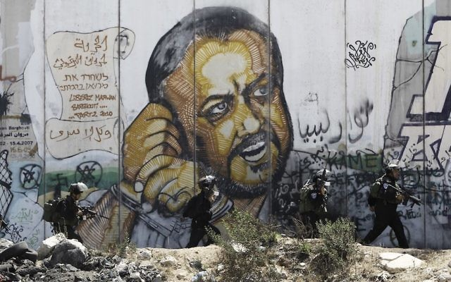 Israeli security officers walking next to a mural of jailed Fatah leader Marwan Barghuti on the West Bank side of Israel's Qalandia checkpoint, July 25, 2014. (Jaafar Ashtiyeh/AFP/Getty Images)