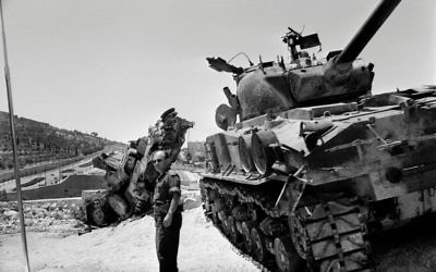 An Israeli soldier checks a destroyed tank on the road between Bethleem and Jerusalem in June 1967 during the six-day war. Getty Images