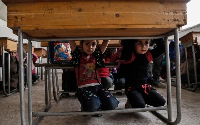 Schoolchildren learn how to protect themselves in case of a bombardment during a war safety awareness class in the rebel-held area of Harasta, on the northeastern outskirts of the capital Damascus, on May 2, 2017. Getty Images