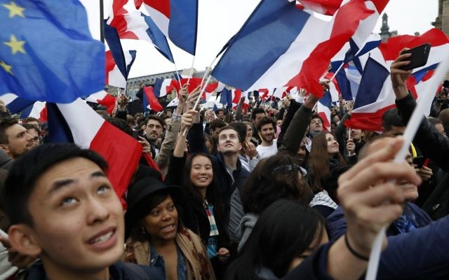 Supporters of the French presidential election candidate for the En Marche ! movement Emmanuel Macron wave French national flags in front of the Pyramid at the Louvre Museum in Paris on May 7, 2017, during the second round of the French presidential election. Getty Images