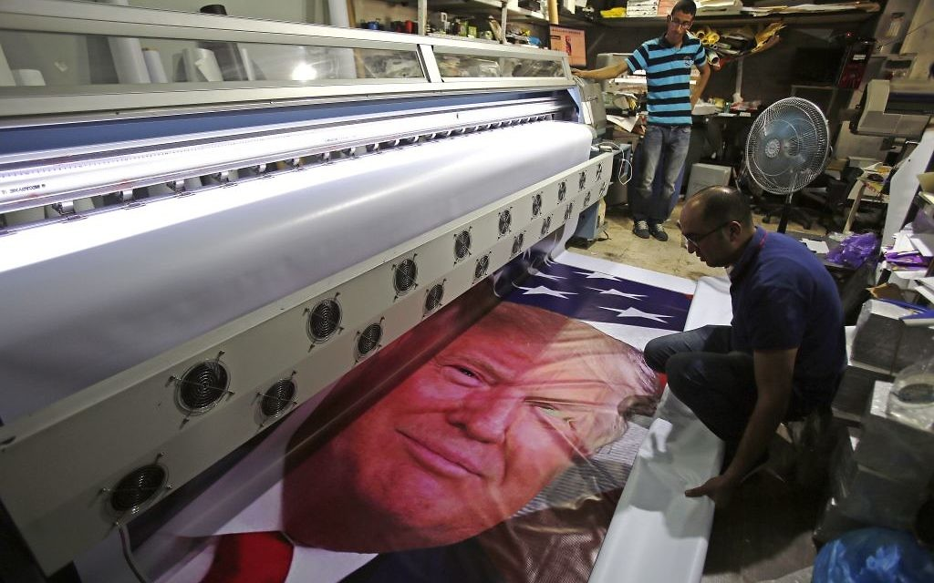 TOPSHOT - Palestinian men print a banner bearing a portrait of US President Donald Trump at a printer's in the West Bank town of Bethlehem, on May 21, 2017, ahead of a two day official visit in Israel and the Palestinian territories. / AFP PHOTO / Musa AL SHAER        (Photo credit should read MUSA AL SHAER/AFP/Getty Images)