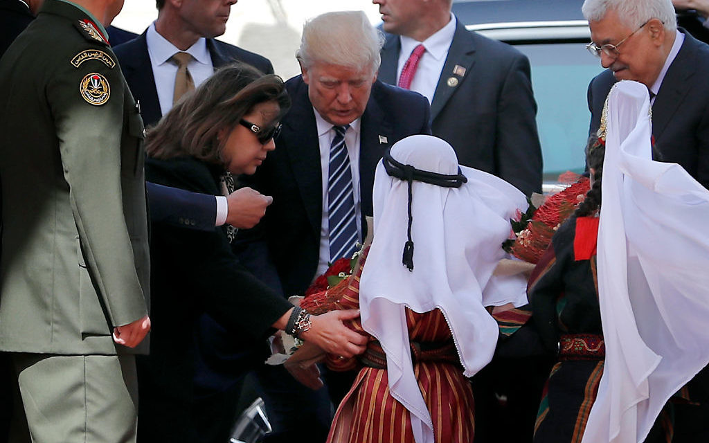 US President Donald Trump (C) is welcomed by Palestinian leader Mahmud Abbas (R) and Palestinian children at the presidential palace in the West Bank city of Bethlehem on May 23, 2017.  / AFP PHOTO / THOMAS COEX        (Photo credit should read THOMAS COEX/AFP/Getty Images)