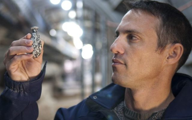 Nahshon Szanton holds a date-shaped glass juglet that was uncovered in excavations in Jerusalem.  The Israel Antiquities Authority unveiled rare relics from the 2,000-year-old battle for the capital that took place on the eve of the destruction of the Second Temple. Courtesy of IAA