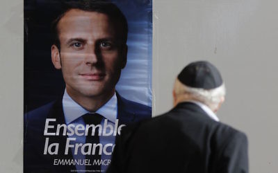 A Jewish man looks at an election poster of the independent centrist French presidential candidate Emmanuel Macron at the French consulate in Jerusalem, on May 7, 2017 during the second round of the French presidential vote. JTA