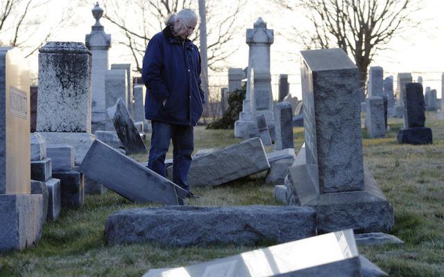 A man looking at fallen tombstones at the Jewish Mount Carmel Cemetery in Philadelphia, Feb. 26, 2017. JTA