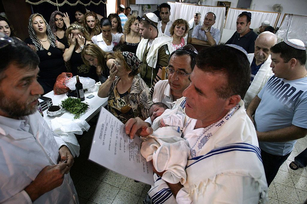 ab3d74acf A father holds his eight-day old son during a bris ceremony. Getty Images