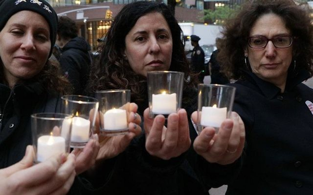 Participants in the vigil hold yahrzeit candles in memory of the St. Louis passengers who died in the Holocaust. Courtesy of HIAS