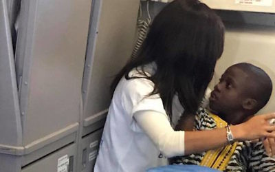 Rochel Groner comforting a child with autism on a flight from Europe to the United States. (Bentzion Groner/Facebook)