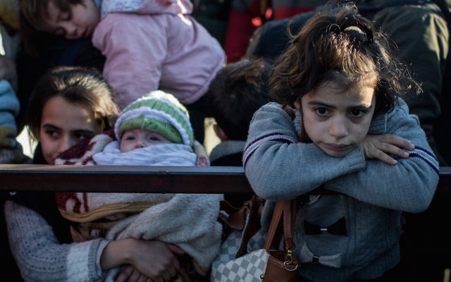 A young girl waiting in line to pass through a border gate as a small number of Syrian refugees are allowed to return to Syria at the closed Turkish border gate in Killis, Feb. 8, 2016. JTA