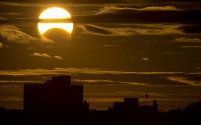 A partial Solar eclipse is seen just after sunrise over the Queens borough of New York across the East River on November 3, 2013 in New York. Getty Images