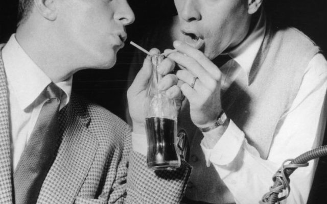 Comedy duo Dean Martin and Jerry Lewis quenching their thirst with a bottle of coke in 1955. Getty Images