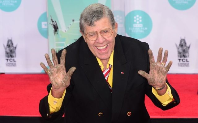 US comedian Jerry Lewis shows his hands at his Hand and Footprint ceremony at the TCL Theater in Hollywood, California on April 12, 2014. He is best known for his slapstick humor in film, television and stage. Getty Images