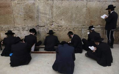 Orthodox Jewish men pray at the Western Wall in Jerusalem's Old City on July 31, 2017, on Tisha B'Av eve. Getty Images