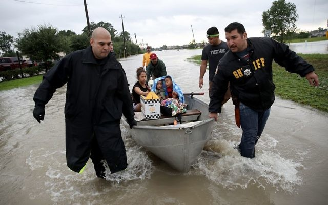 The Tellez family is evacuated from their home after severe flooding following Hurricane Harvey in north Houston August 29, 2017 in Houston, Texas. Getty Images
