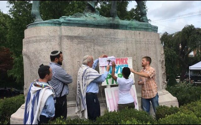 "Rabbi Weiss, Rabbi Uri Topolosky and Rabbi Shmuel Herzfeld join Aliya and Tom as they place a placard in memory of Heather"" at the site of the statue. Courtesy of Rabbi Shmuel Herzfeld"