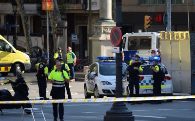 Medical personnel and policemen stand in a cordoned-off area after a van plowed into the crowd in Barcelona, Aug. 17, 2017.  JTA