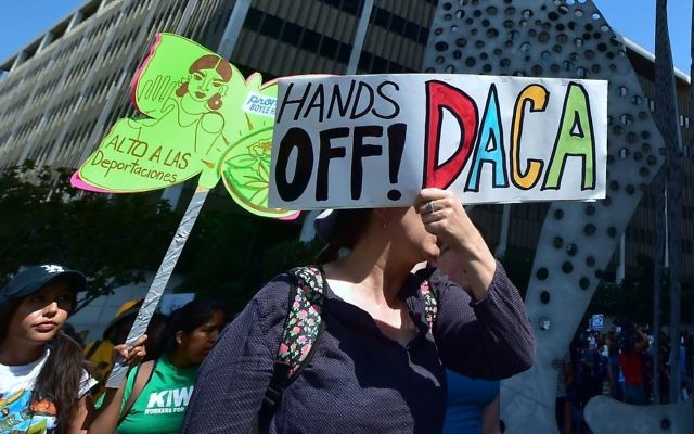 Young immigrants and supporters walk holding signs during a rally in support of Deferred Action for Childhood Arrivals (DACA) in Los Angeles, California on September 1, 2017.  Getty Images