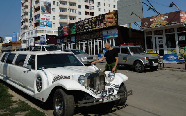 An Israeli visitor to Uman examining a Ukrainian luxury limousine parked on the city's heavily Jewish Pushkin Street, Sept. 8, 2017. (Cnaan Liphshiz)