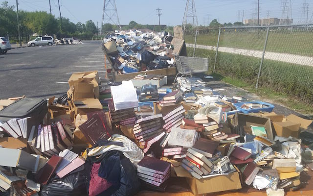 Piles of ruined books from United Orthodox Synagogues of Houston. The congregation lost many of its prayer books and replenished them through donations. JTA