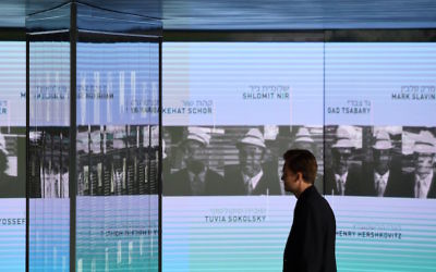 A visitor looking at the portraits of the Israeli Olympians murdered at the 1972 Munich games at a new memorial in the German city, Sept. 6, 2017. (Christof Stache/AFP/Getty Images)