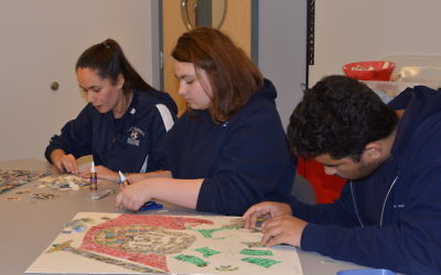 """Foxborough Regional Charter School High school students selecting stamps to use on two Holocaust Stamp Project stamps collages, """"I Am the Last Witness"""" and """"White Rose."""" JTA"""