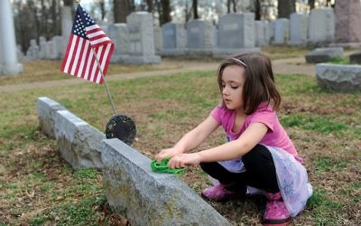 A child cleans graffiti off a headstone at a St. Louis-area Jewish cemetery after it was vandalized in February. GETTY IMAGES