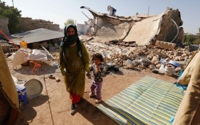 An Iranian woman and child walking in rubble of their home in the village of Kouik two days after a major earthquake struck Iran near the Iraq border. (Atta Kenare/AFP/Getty Images)