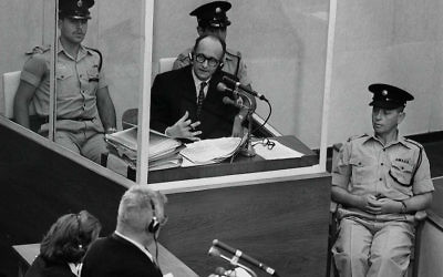 Nazi war criminal Adolf Eichmann standing in a protective glass booth flanked by Israeli police during his trial in Jerusalem, June 22, 1961. JTA