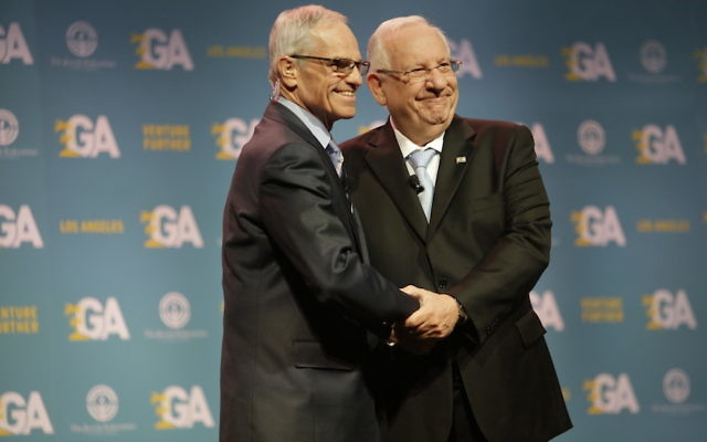 Israeli President Reuven Rivlin, right, shaking hands with Richard Sandler, board chairman of the Jewish Federations of North America, at the group's General Assembly in Los Angeles, Nov. 13, 2017. (Jeffrey Brown/JFNA)