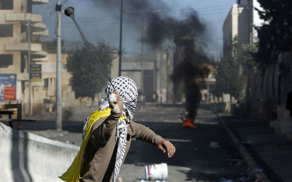 A Palestinian protestor throws a rock towards Israeli security forces during clashes Tuesday in Bethlehem. The protests come in the wake of President Donald Trump's declaration of Jerusalem as Israel's capital. Getty Images